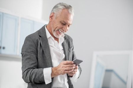 Good news. Happy pensioner expressing positivity and bowing head while looking at his gadget