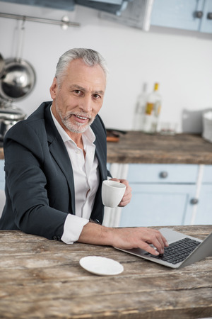 Be confident. Cheerful businessman expressing positivity and holding cup in left hand while sitting in front of his computer Stockfoto