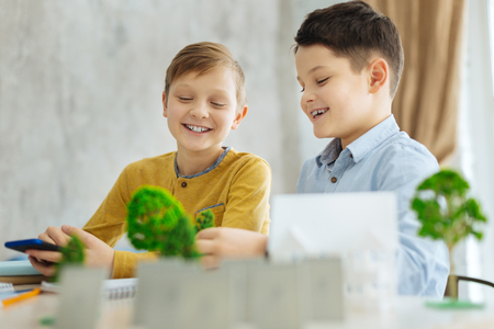 Interesting home assignment. Two upbeat pre-teen boys sitting at the table and creating the model of the miniature neighborhood for their ecology project together