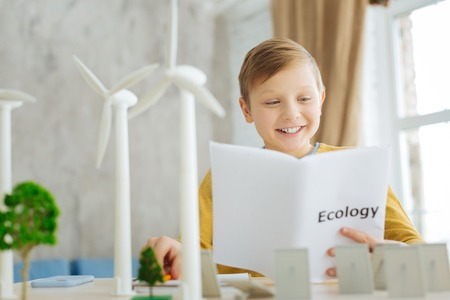 Young researcher. Upbeat pre-teen boy reading about alternative sources of energy in the ecology book while having wind turbine models and solar panel models in front of him