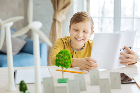 Thirst for knowledge. Charming pre-ten boy studying a book dedicated to ecology while looking at the miniatures of trees, solar panels and wind turbines