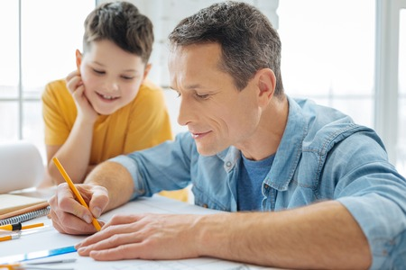 Peaceful process. Charming young engineer using a pencil and a ruler, drawing a blueprint with a peaceful smile on his lips, while his boy watching at his work in awe Imagens