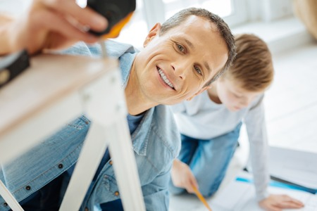 Happy carpenter. The close up of a cheerful young man measuring the leg of a table with the help of a measuring tape and smiling while his son studying the blueprint Reklamní fotografie