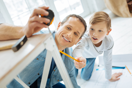 Eager to help. Excited pre-teen boy checking the length of a table leg by looking at the tape measure his father holding for him Stock Photo
