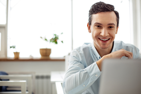 Good mood. Attractive alert dark-eyed dark-haired man smiling and working on his laptop while sitting at the table