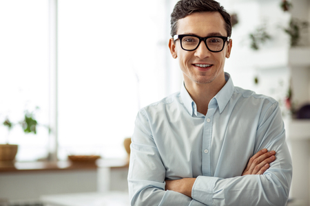 I feel happy. Attractive joyful dark-haired man smiling and wearing glasses and having his arms crossed Reklamní fotografie