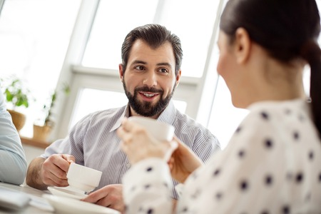 Happy friends. Handsome exuberant bearded man drinking coffee and smiling and talking with his female friends