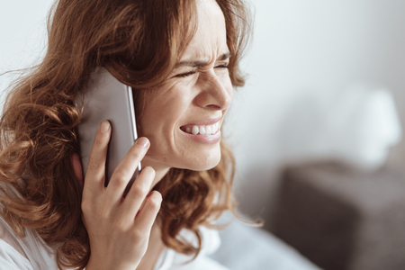 Young lady having emotional disorder grimacing while calling somebody during another nervous breakdown. Stock Photo
