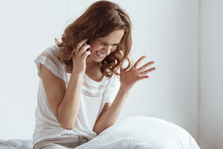 Completely emotionally exhausted woman gesturing and getting angry while having a phone conversation.