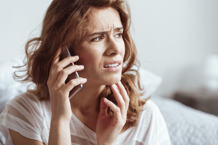 Irritated lady looking into vacancy while sitting at home and listening to someone taking on phone.