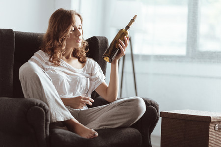Emotionally exhausted lady sitting on sofa and looking at a bottle of wine while trying to relief her emotional pain.