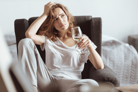 What should I do. Confused stressed woman trying to solve her problem and drinking white wine at home. Stock Photo