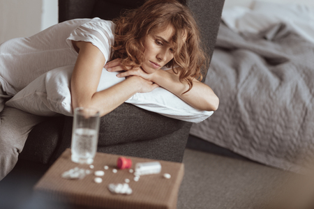 Suicidal thoughts. Depressed woman sitting on a sofa and thinking about her life while looking at pills lying on a table. Stock Photo