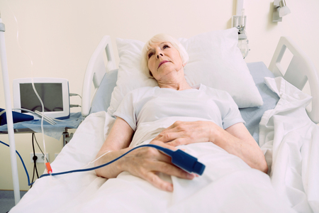 Getting better every day. Poor senior woman thinking about something pleasant while lying in a hospital bed with a heart rate medical equipment. Stock Photo