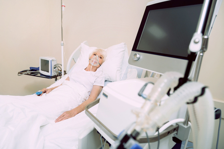 Wish I was at home right now. Poor retired lady focusing her attention on a computer while lying in a hospital bed with a pulse oximeter and a respiratory support. Stock Photo