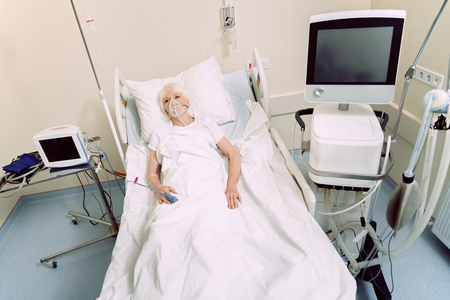 Having some health problems. Top view on an elderly lady with an oxygen mask and a heart rate medical equipment lying in a hospital bed.