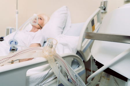 Modern medicine. Selective focus on a respiratory support of a retired lady sleeping in the background while wearing an oxygen mask.