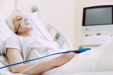 Fragile heart. Selective focus on a hand of a poor woman lying in a hospital bed with a heart rate medical equipment.