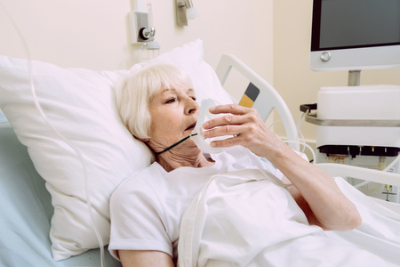 Serious health problems. Exhausted retired lady looking sad while lying in a hospital bed and holding her oxygen mask while undergoing treatment. Stock Photo