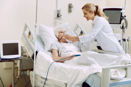 DO not worry. Friendly female medical worker smiling while helping her retired patient and adjusting an oxygen mask at hospital. Stockfoto