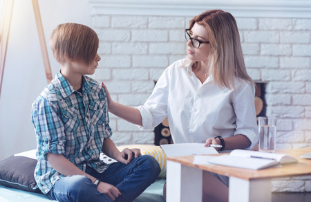 Careful psychology professional putting her hand on a shoulder of a young patient while talking to him and trying to calm him down.