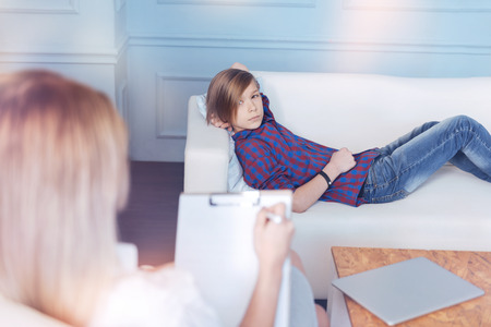 Male youngster in casual attire relaxing on a sofa and looking at a professional doctor during a psychological session.