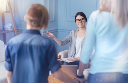 Young professional wearing glasses looking at a family standing in front and welcoming them at her personal office. Stock Photo