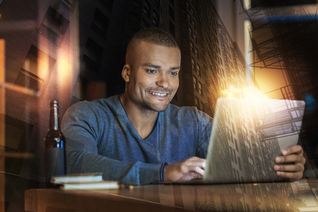 Very nice. Optimistic cheerful man being in a good mood while sitting at the table and looking at the screen of a laptop Foto de archivo