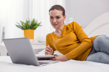 Busy day. Ambitious appealing female freelancer posing on bed while staring at screen and using notebook