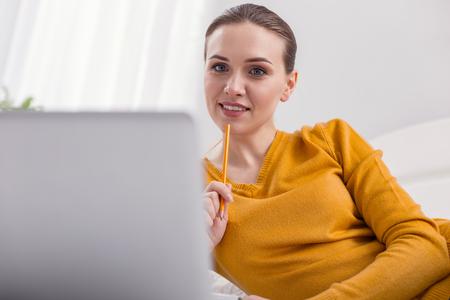 Freelance project. Thoughtful reflective female freelancer holding pencil while smiling and thinking