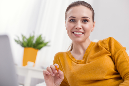 Time to work. Cheerful glad female freelancer using pencil while grinning and looking at camera
