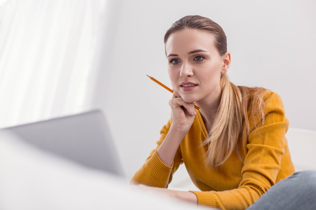 Little concern. Musing pleasant female freelancer holding pencil while touching face and posing on light background Stockfoto