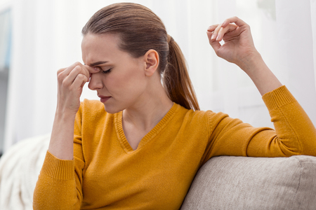 Horrible headache. Sick exhausted beautiful woman massaging nose bridge while turning head in profile and posing on the light background Stock Photo