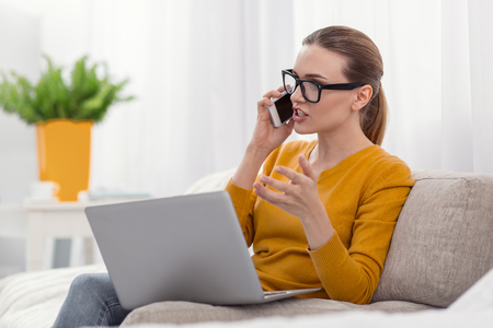 Business problem. Unsatisfied displeased attractive businesswoman talking on phone while wearing glasses and working Stockfoto