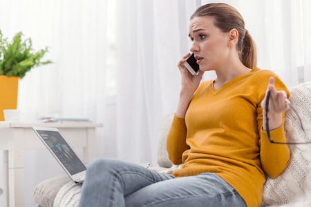 Uncertain situation. Beautiful mad young businesswoman communicating on phone while carrying glasses and frowning Stock Photo