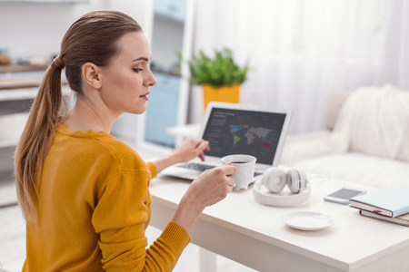 Lets work. Ambitious focused skillful businesswoman drinking coffee while posing in profile and working Stockfoto