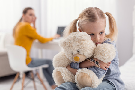 Bad mood. Vulnerable displeased pleasant girl embracing plush bear while staring aside and sitting on the blurred background