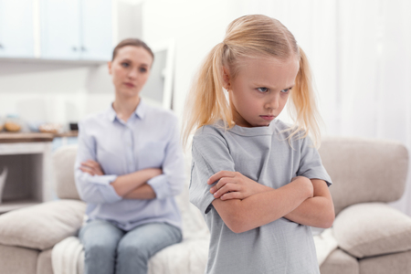 Huge offense. Unsatisfied angry displeased girl crossing arms while frowning and turning with back to mom