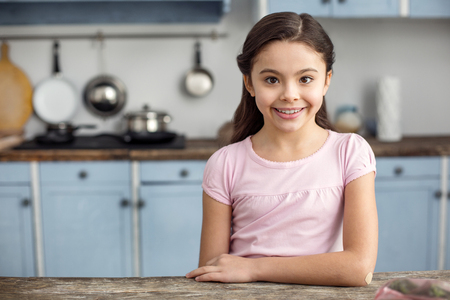 I feel happy. Beautiful inspired dark-haired little girl smiling and sitting at the table in the kitchen and wearing a pink shirt
