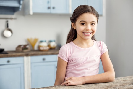 Happiness inside me. Pretty cheerful dark-haired little girl smiling and sitting at the table in the kitchen and wearing a pink shirt