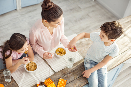 Breakfast together. Athletic dark-haired young mother smiling and giving vitamins to her son sitting on the table and her daughter having breakfast
