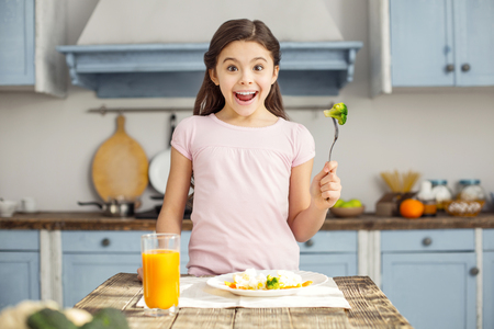 I am healthy. Beautiful exuberant dark-haired little girl smiling and having healthy breakfast and drinking some juice