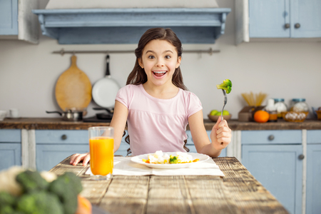 So delicious. Beautiful content dark-haired little girl smiling and having healthy breakfast and drinking some juice Foto de archivo - 96316439