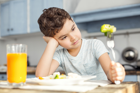 I want candies. Handsome sad dark-haired little boy having healthy breakfast and looking at the green vegetable on his fork and not liking it Stock Photo