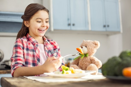 So appetizing. Beautiful exuberant dark-haired little girl smiling and feeding her toy with healthy food while sitting at the table in the kitchen Stock Photo