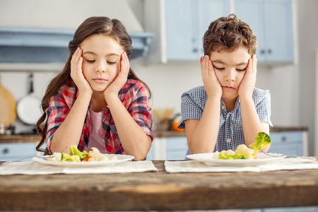 We detest vegetables. Attractive unhappy dark-haired little brother and sister sitting at the table and having healthy breakfast and looking sadly at the vegetables