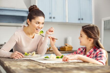 Glückliche Kindheit. Schöne wachsame dunkelhaarige junge Mutter, die gesundes Lebensmittel mit ihrer Tochter und ihrem Mädchen einzieht sie lächelt und isst