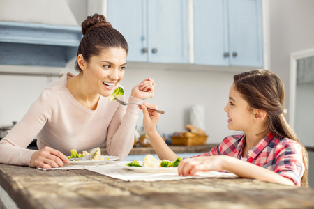 Happy childhood. Beautiful alert dark-haired young mother smiling and eating healthy food with her daughter and her girl feeding her Foto de archivo