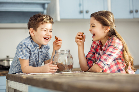 Joking. Cute happy little dark-haired brother and sister laughing and eating cookies while sitting at the table Standard-Bild - 96316264