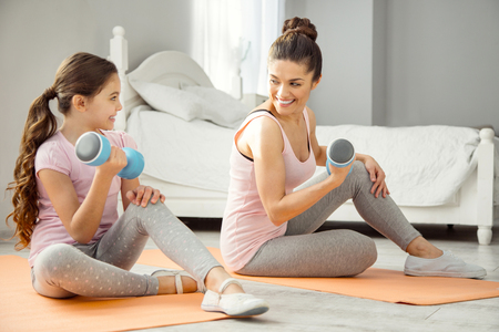 Exercising arms. Pretty alert young dark-haired mother doing some exercises with hand weights with her daughter while sitting on the floor and looking at her girl